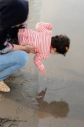 Mother and young child at beach playing with water