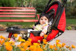 Little baby girl in colorful cloth sitting in modern carriage