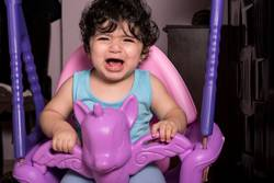 Crying little baby girl on unicorn swing