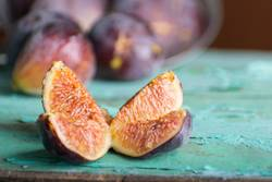 Sliced ripe purple fig on turquoise wooden table
