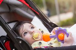 Little baby with yellow dummy resting at baby carriage