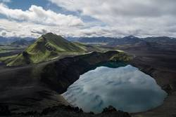 Mirror lake in the Icelandic highlands with lush green mountains
