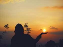 Beautiful Silhoutte and Sunset and Woman holding Sun in hand