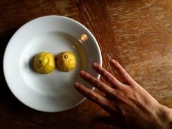 Hand streckt sich nach Zitrone