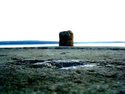 einsamer Poller vor der weiten See