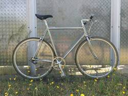 silbernes single speed fahrrad vor metallwand