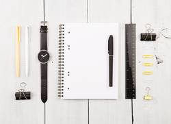 Workplace with notepad, watch, pens and other office supplies
