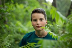 Portrait of young beautiful teen boy in forest