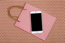 shopping bag, gift bags and white smartphone