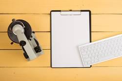 microscope, blank clipboard, computer keyboard on yellow desk