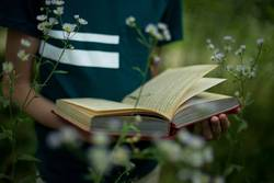 teenager is holding a book in his hands in nature