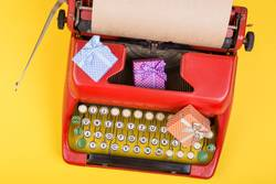 red typewriter with paper, gift boxes on yellow background