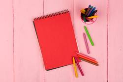 Blank red note pad and crayons on pink wooden table